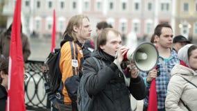 Jonge mens die met een megafoon bij de protestmanifestatie schreeuwen