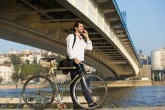 Jonge mens die met fiets lopen en op mobiele telefoon spreken Stock Foto