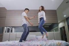 Jonge mens die met haar vrouw op het bed dansen stock foto