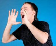 Jonge mens die met handen schreeuwt die aan zijn mond tot een kom worden gevormd stock foto's