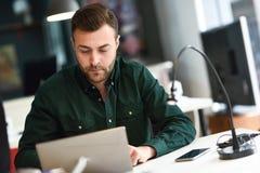 Jonge mens die met laptop computer op wit bureau bestuderen stock afbeeldingen
