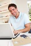 Jonge mens die met laptop computer werkt stock fotografie