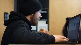 Jonge mens die met laptop in een koffie werken stock videobeelden