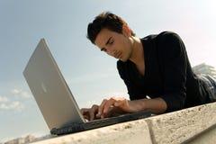 Jonge mens die met laptop werkt Royalty-vrije Stock Foto