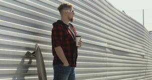 Jonge mens die met longboard en het drinken koffie blijven stock videobeelden