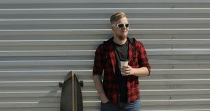 Jonge mens die met longboard en het drinken koffie blijven stock footage