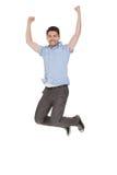Jonge mens die met opgeheven wapens springen Stock Foto
