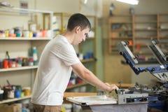 Jonge mens die met rubberschuiver aan fabriek werken stock fotografie