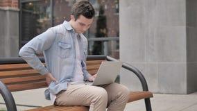 Jonge mens die met rugpijn aan openlucht laptop werken stock video