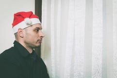 Jonge mens die met Santa Claus-hoed door venster kijken die eenzaam en droevig voor Nieuwjaar en Kerstmis het concept van de vaka stock fotografie