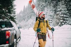 Jonge mens die met ski in het sneeuw de winterbos lopen Stock Afbeeldingen