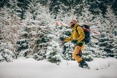 Jonge mens die met ski in het sneeuwbos lopen Royalty-vrije Stock Afbeeldingen