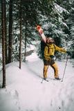 Jonge mens die met ski in het sneeuwbos lopen Stock Fotografie