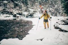 Jonge mens die met ski in het sneeuwbos lopen Royalty-vrije Stock Afbeelding