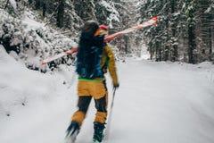 Jonge mens die met ski in het sneeuwbos lopen Stock Afbeeldingen