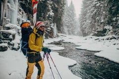 Jonge mens die met ski in het sneeuwbos lopen Stock Afbeelding
