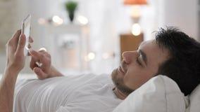 Jonge mens die met telefoon Internet in slaapkamer doorbladeren stock footage