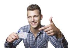Jonge mens die met zijn bestuurdersvergunning pronken royalty-vrije stock foto's