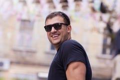 Jonge mens die met zwarte zonnebril op de straat lachen Stock Fotografie