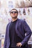 Jonge mens die met zwarte zonnebril op de straat lachen Stock Foto's