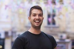 Jonge mens die met zwarte zonnebril op de straat lachen Stock Afbeeldingen