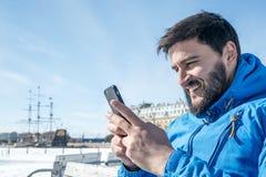 Jonge mens die mobiele telefoon in de stad houden stock afbeelding
