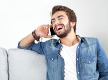 Jonge mens die mobiele telefoon en het lachen spreken Stock Fotografie