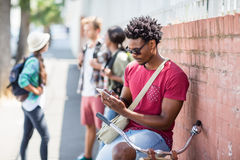 Jonge mens die mobiele telefoon met behulp van stock fotografie