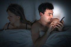 Jonge mens die mobiele telefoon met behulp van, terwijl zijn vrouwenslaap bij nacht Royalty-vrije Stock Afbeelding
