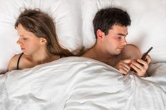 Jonge mens die mobiele telefoon met behulp van, terwijl zijn vrouwenslaap bij nacht Royalty-vrije Stock Foto's