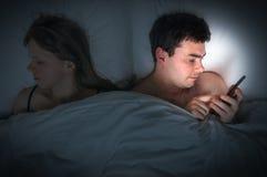 Jonge mens die mobiele telefoon met behulp van, terwijl zijn vrouwenslaap bij nacht Stock Fotografie