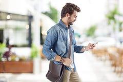 Jonge mens die mobiele telefoon in straat met behulp van Stock Foto