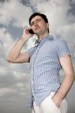 Jonge mens die mobiele telefoon uitnodigt, openlucht Royalty-vrije Stock Afbeelding