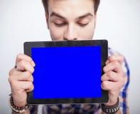 Jonge mens die neer terwijl het houden van een computer van het tabletstootkussen kijken Royalty-vrije Stock Afbeelding