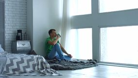 Jonge mens die ochtend van koffie genieten door het venster stock footage