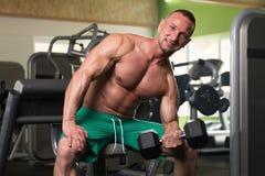Jonge Mens die Oefening voor Bicepsen met Domoor doen Stock Afbeelding