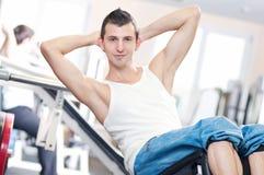 Jonge mens die oefeningen doet bij gymnastiek Stock Fotografie