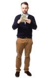 Jonge mens die omhoog een handvol van geld eyeing stock foto