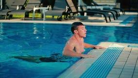 Jonge mens die onder het water in de pool zwemmen stock video