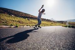Jonge mens die onderaan de weg met een skateboard rijden Stock Foto