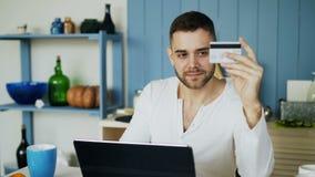 Jonge mens die online het winkelen hebben gebruikend creditcard en laptop computer terwijl ontbijt thuis in de keuken hebben stock video