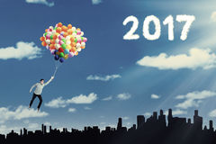Jonge mens die op ballons vliegen Royalty-vrije Stock Afbeeldingen