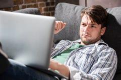 Jonge mens die op bank liggen en laptop, kleine bedrijfsmensenconcept met behulp van Royalty-vrije Stock Afbeeldingen