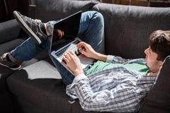 Jonge mens die op bank liggen en laptop, kleine bedrijfsmensenconcept met behulp van Royalty-vrije Stock Afbeelding