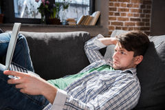 Jonge mens die op bank liggen en laptop, kleine bedrijfsmensenconcept met behulp van Stock Afbeeldingen