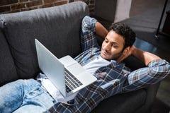 Jonge mens die op bank met laptop, kleine bedrijfsmensenconcept liggen Stock Afbeelding