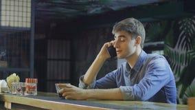 Jonge mens die op cellphone en het drinken alcohol spreken stock video