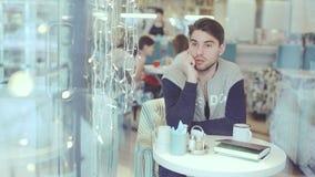 Jonge mens die op celtelefoon spreken in koffie stock video