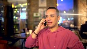 Jonge mens die op celtelefoon spreken in koffie Aantrekkelijke Spaanse mens een zakenman, een student of een opstarten met stock video