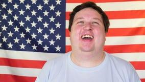 Jonge mens die op de achtergrond van een vlag van de V.S. lachen stock videobeelden